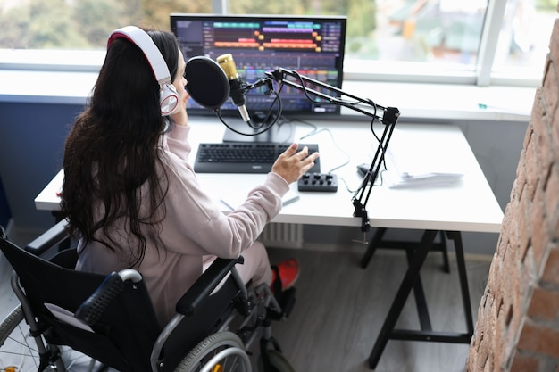 Une femme en fauteuil roulant avec un casque parle dans un microphone devant un écran d'ordinateur