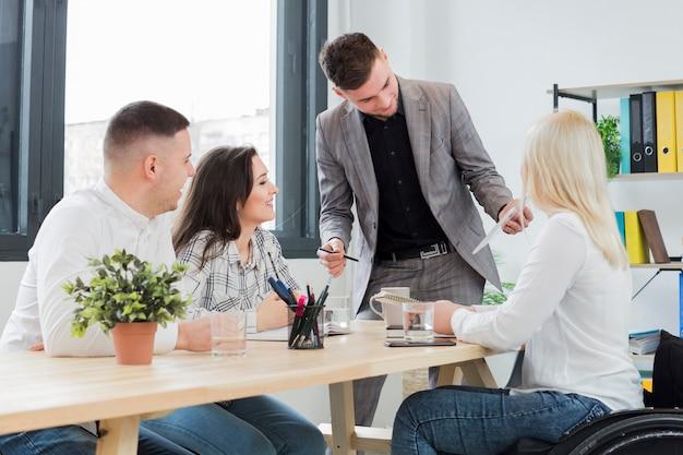 Femme en fauteuil roulant avec des collègues lors d'une réunion