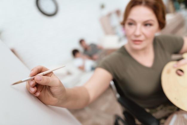 Une femme en fauteuil roulant dessine sur une toile.