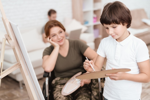Une femme en fauteuil roulant regarde son fils peindre sur une toile.