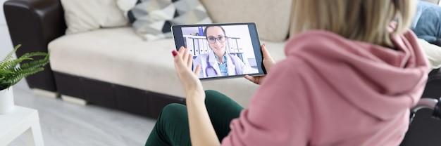 Femme En Fauteuil Roulant Tenant Une Tablette Avec Photo Agrandi. Concept De Consultations Médicales En Ligne Photo Premium