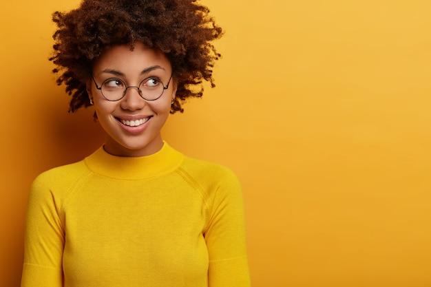 Une femme féminine heureuse regarde avec le sourire de côté, a une attitude optimiste, attend que la bonne chose se produise, se concentre mystérieusement sur l'annonce de la promo, porte des lunettes rondes, un pull jaune.