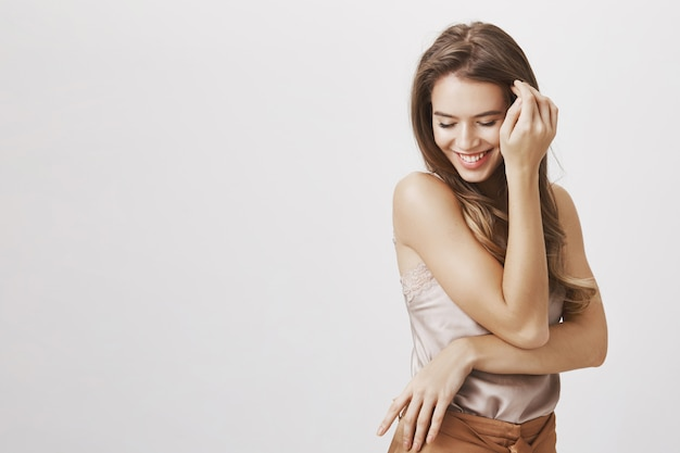 Femme féminine regarde vers le bas, souriant et touche les cheveux