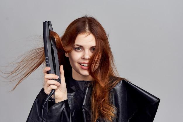 Femme en fer à friser peignoir noir à la main peigne de soins capillaires coiffure à la mode