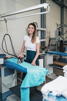 Femme avec fer travaillant à l'atelier de repassage. services de nettoyage.