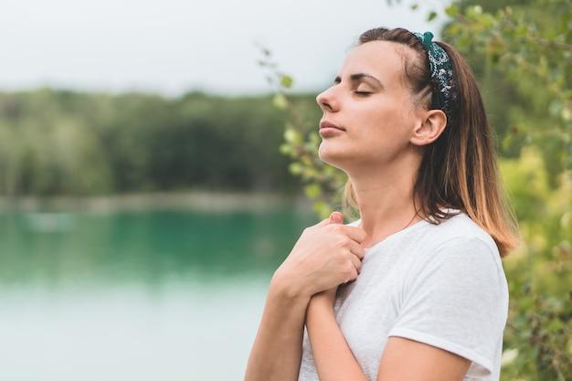 La femme ferma les yeux, priant à l'extérieur. mains jointes dans le concept de prière pour la foi, la spiritualité et la religion