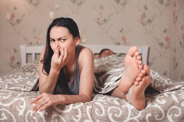 La femme a fermé le nez une main d'une odeur désagréable des pieds du mari