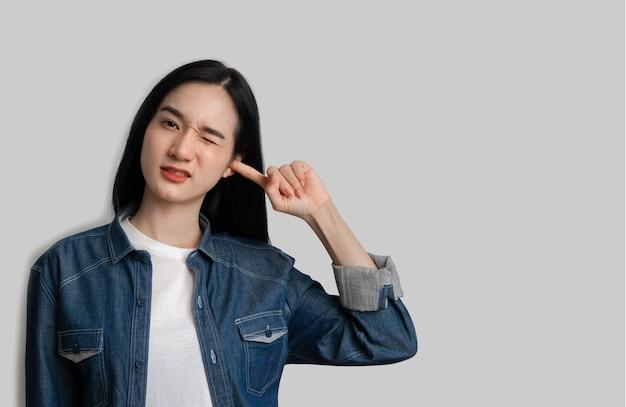 Femme a fermé ses oreilles pour ne pas écouter sur fond gris
