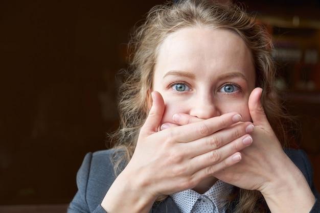 Femme ferme ta bouche avec tes mains. silence, geste, pas de potins, secret