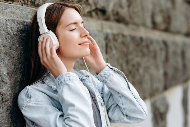 Femme fermé les yeux et écouter de la musique dans des écouteurs avec plaisir en plein air