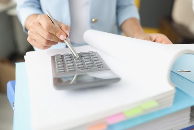 Femme feuilletant un dossier avec des documents et regardant la calculatrice en gros plan