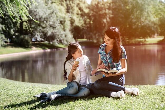 Femme et fille assise ensemble sur l'herbe au bord de l'eau.