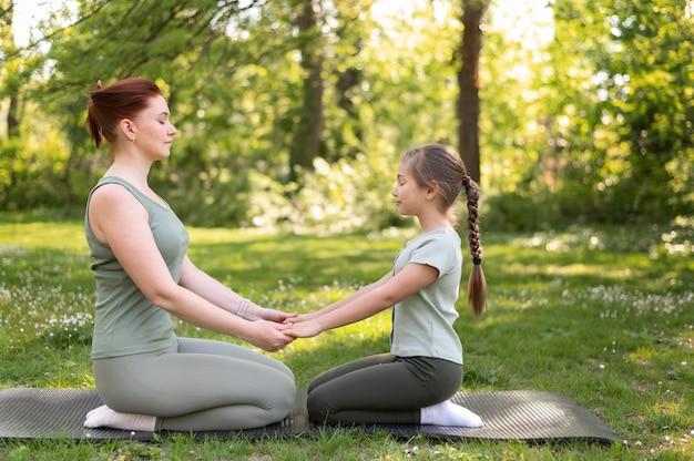 Femme et fille assise sur un tapis