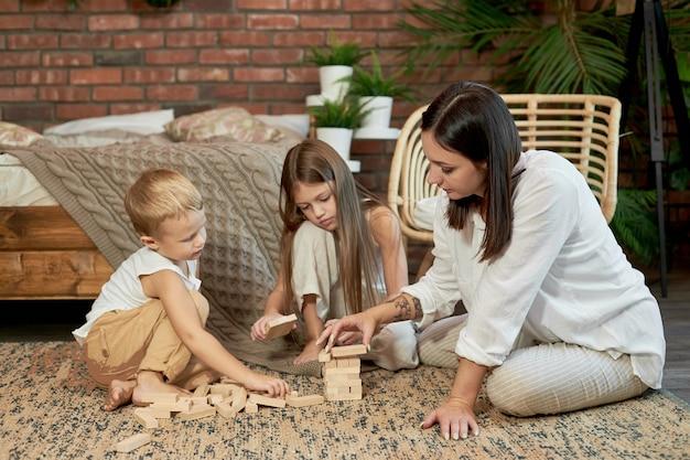 Femme fille et garçon jouent au jeu de puzzle familial