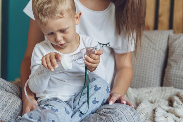 Femme avec fils faisant l'inhalation avec nébuliseur dans leur chambre à la maison