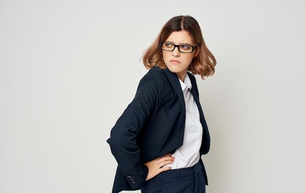 Femme de finance d'entreprise en costume classique sur une vue latérale du mur léger.