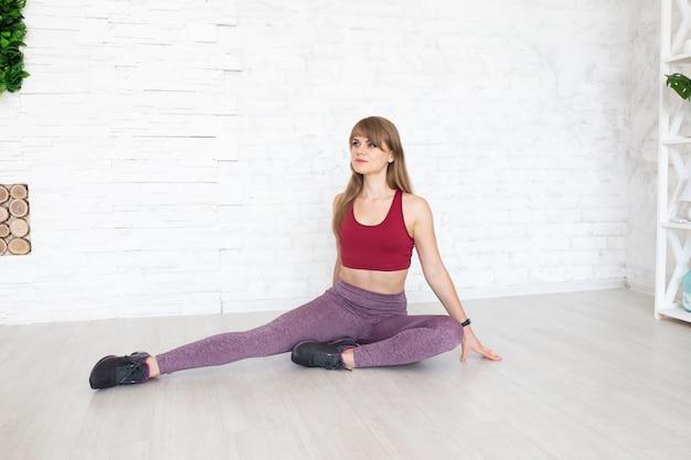 Femme fitness assis sur le sol concept de sport féminin. femme sportive en vêtements de style sport sur le sol. copyplace, espace de copie.