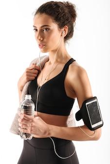 Femme fitness brune assez bouclée avec bouteille