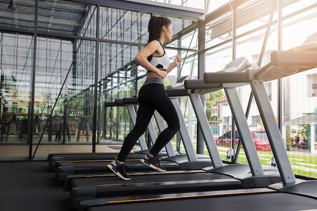 Femme fitness en cours d'exécution sur la machine en cours d'exécution.