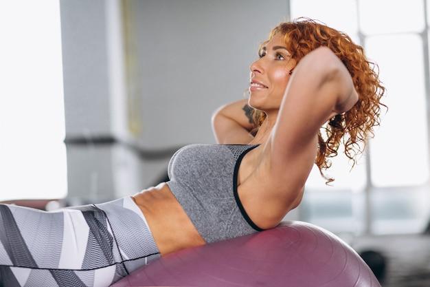 Femme fitness, faire, abd sur, balle, à, gymnase