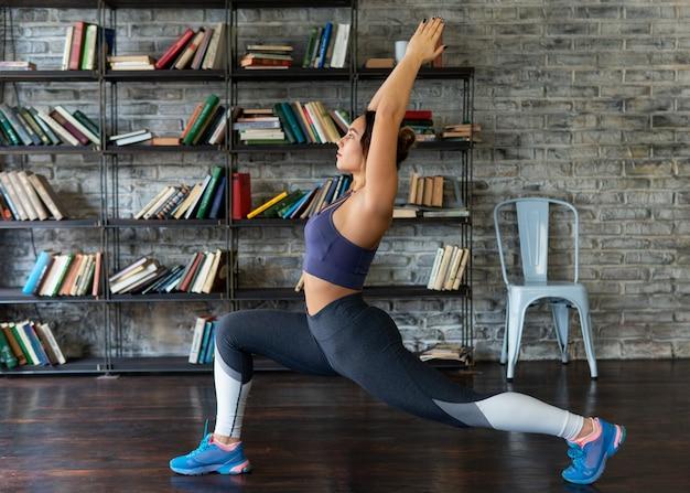 Femme fitness, faire, fente avant, pendant, yoga, chez soi