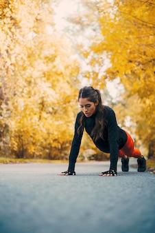 Femme fitness faisant des pompes dans parc automne.