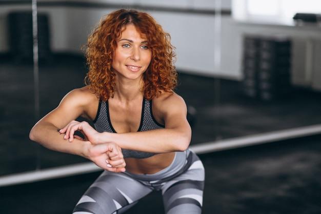 Femme fitness faisant des squats au gymnase