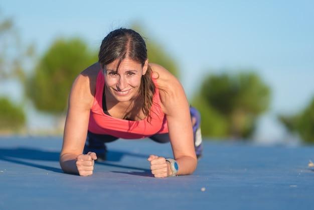 Femme fitness faisant des tractions au cours de l'entraînement croisé en plein air