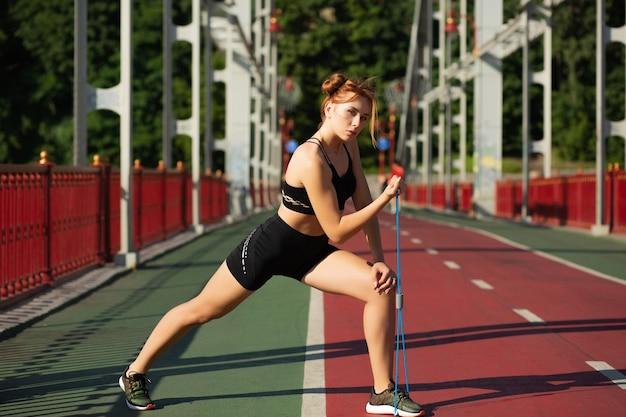 Femme de fitness forte faisant des étirements avec la bande de résistance en caoutchouc sur le pont. espace pour le texte