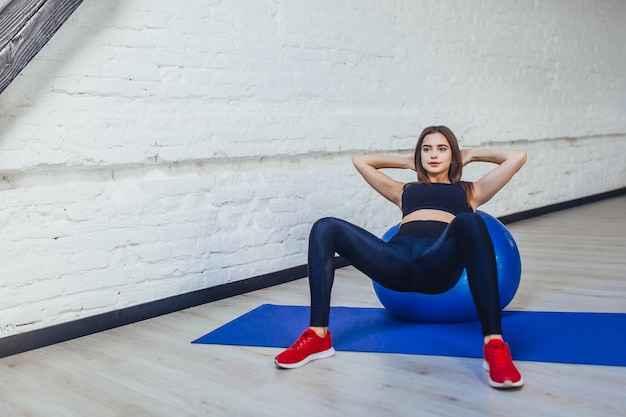 Femme fitness pratiquant avec ballon de fitness bleu.