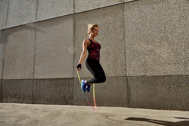 Femme fitness, sauter en plein air en milieu urbain.
