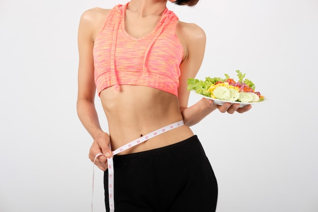 Femme fitness sportive sportswear avec salade de légumes sur blanc
