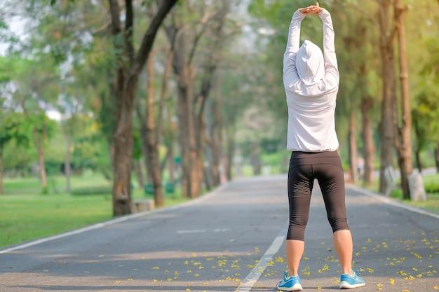Femme de fitness streching dans le parc