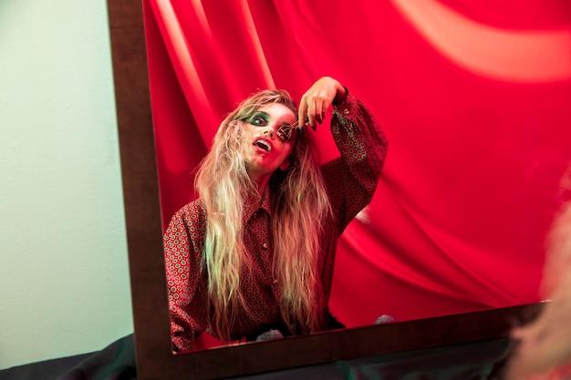 Femme fixant ses cils dans le miroir