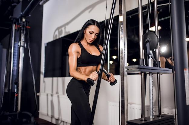 Femme, fléchir, muscles, câble, machine, gymnase