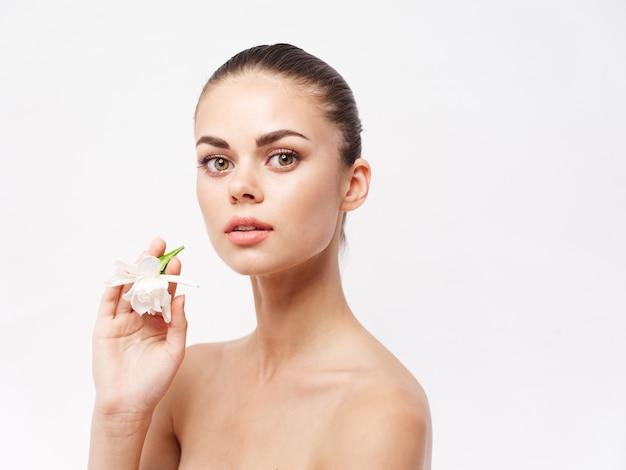 Femme avec une fleur dans ses mains épaules nues cosmétiques look attrayant