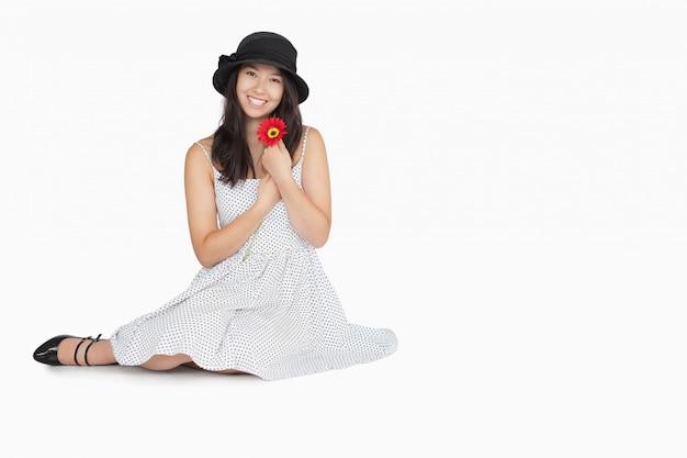 Femme avec fleur en robe assis sur le sol
