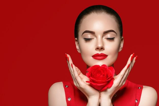Femme avec fleur rose. portrait féminin de beauté avec de beaux ongles de manucure de fleur rose et coiffure de salon sur fond rouge