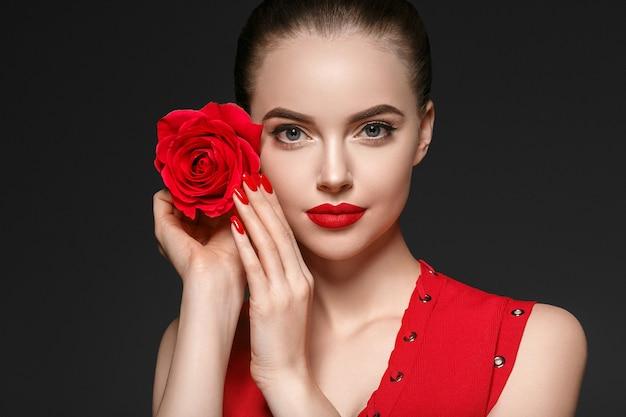 Femme avec fleur rose. portrait de femme de beauté avec une belle fleur rose et une coiffure de salon sur fond gris. prise de vue en studio.