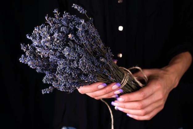 Femme fleuriste attachant un bouquet frais à la lavande
