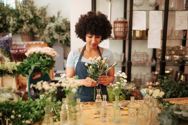 Femme fleuriste avec bouquet de fleurs debout dans la boutique