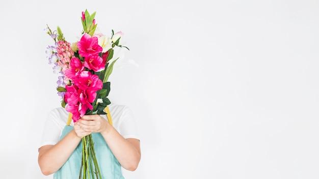 Femme fleuriste cache son visage derrière un bouquet de fleurs sur fond blanc