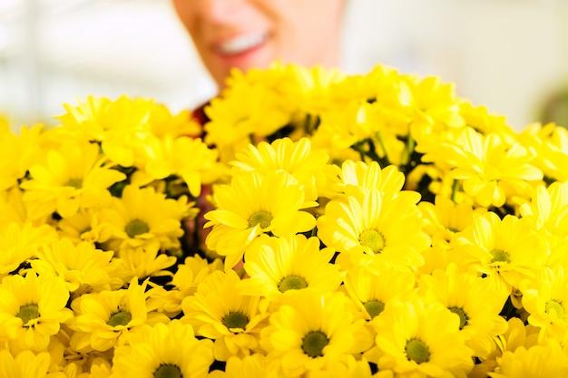 Femme fleuriste dans un magasin de fleurs