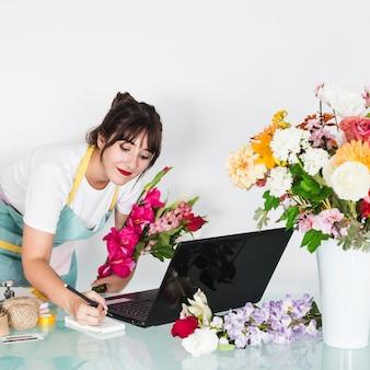 Femme fleuriste écrit sur le bloc-notes dans un magasin de fleurs