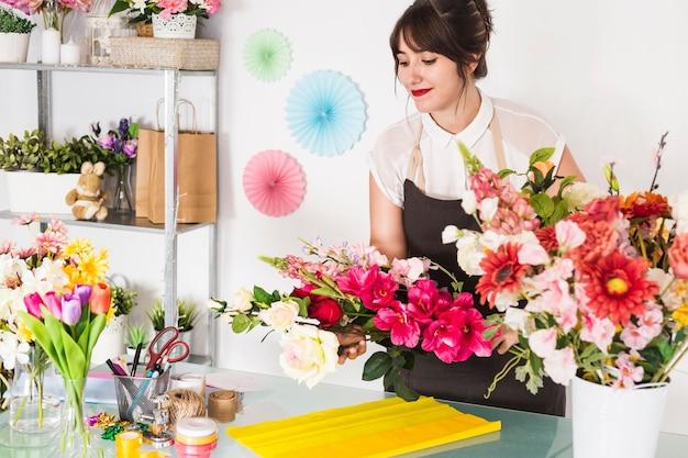 Femme fleuriste faisant un bouquet de fleurs dans un magasin de fleurs