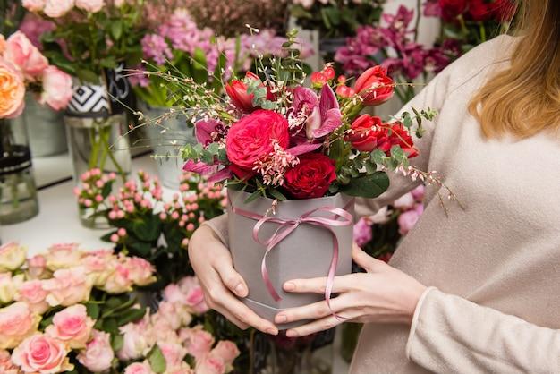 Femme fleuriste mains organisant la composition florale