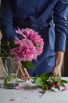 Femme, fleuriste a mis une pivoine dans un vase. belles pivoines roses dans un bocal. fermer.