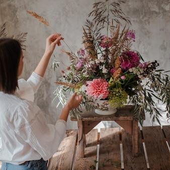 Femme fleuriste professionnel prépare l'arrangement de fleurs sauvages