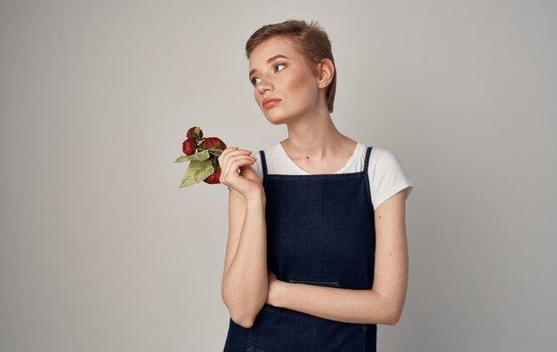 Femme avec des fleurs de coupe courte dans les mains de cosmétiques de style élégant