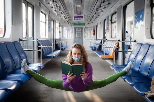 Femme flexible assise sur la scission dans le métro et livre de lecture